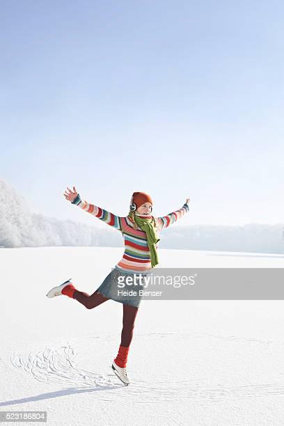 woman balancing on one ice skate - スケート ストックフォトと画像