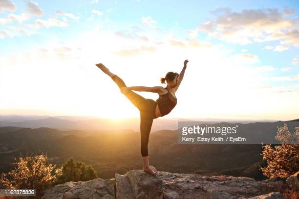 woman balancing on rock at mountain against sky during sunset - kerry estey keith stock photos and pictures