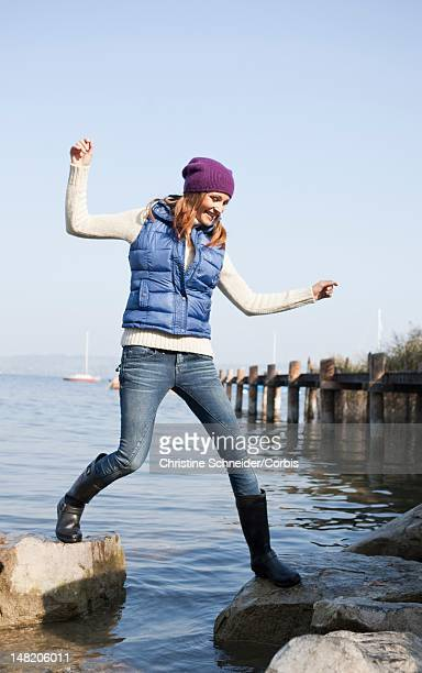woman balancing on stones at lake - gummistiefel frau stock-fotos und bilder