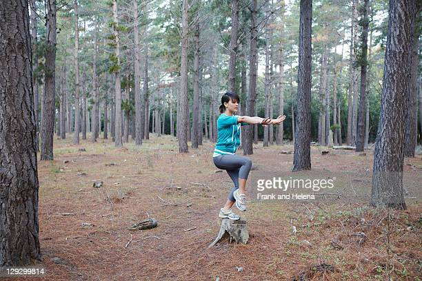 Woman balancing on stump in forest