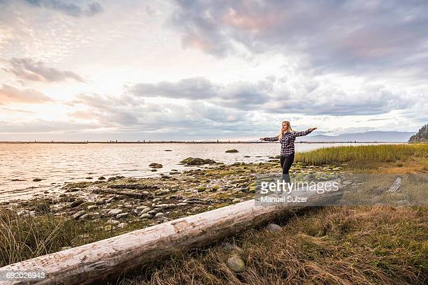 Woman balancing on tree trunk at Wreck Beach, Vancouver, Canada