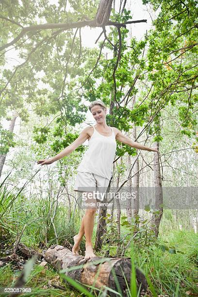 Woman balancing on tree trunk in forest