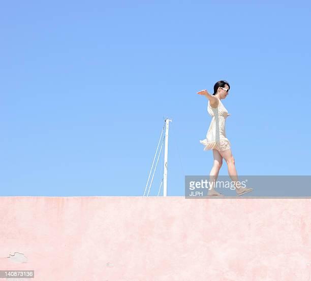 Femme en équilibre sur le mur