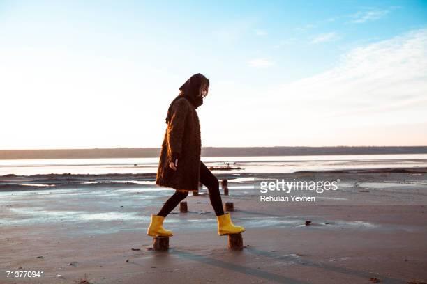 woman balancing on wooden stumps on beach - gummistiefel frau stock-fotos und bilder