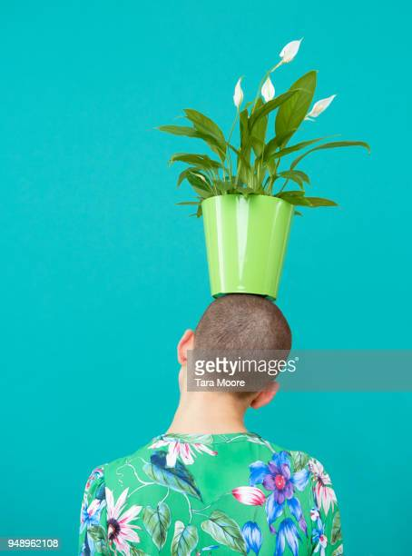 woman balancing pot plant on head