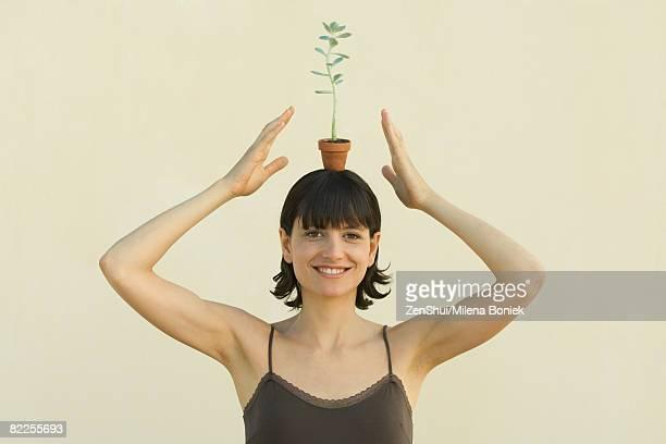 woman balancing small potted plant on head, smiling at camera, portrait - cami fotografías e imágenes de stock