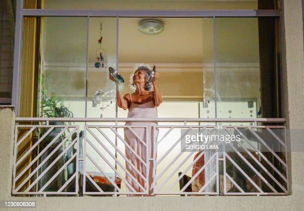 Woman bangs saucepan lids from a window of her apartment as a protest against President Jair Bolsonaro as he delivers a speech on TV, in Brasilia, on...