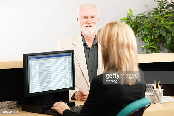 Woman Bank Teller at Retail Banking Counter Serving Customer Hz