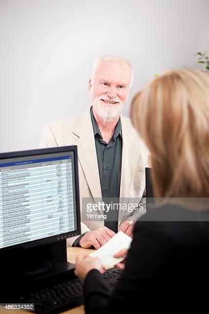 Woman Bank Teller at Retail Banking Counter Serving Customer