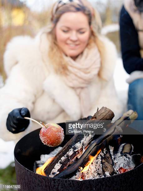 Woman barbecuing in winter, smiling
