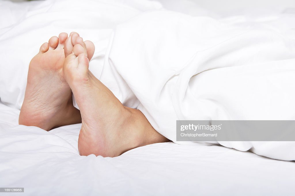 Woman bare feet under blanket : Stock Photo