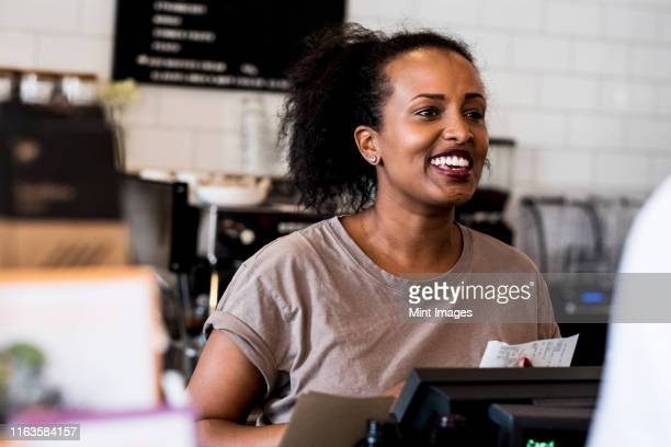 a woman barista smiling in welcome beside the counter in a coffee shop. - real people stock pictures, royalty-free photos & images