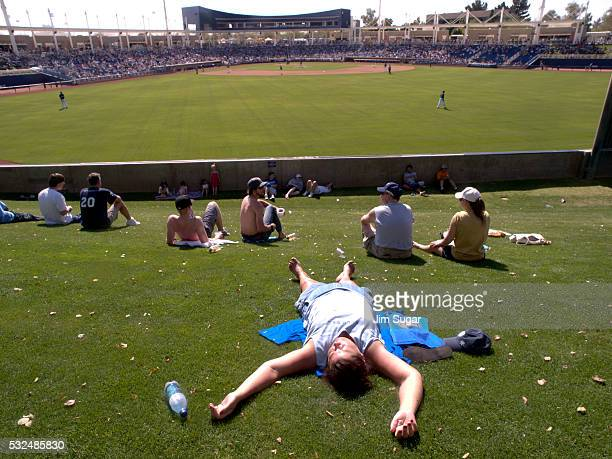 A woman baseball fans soaks in the sun during a spring training game between the Milwaukee Brewers and Colorado Rockies