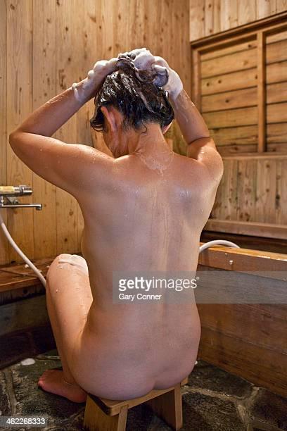 Woman bathes before soaking in hot bath