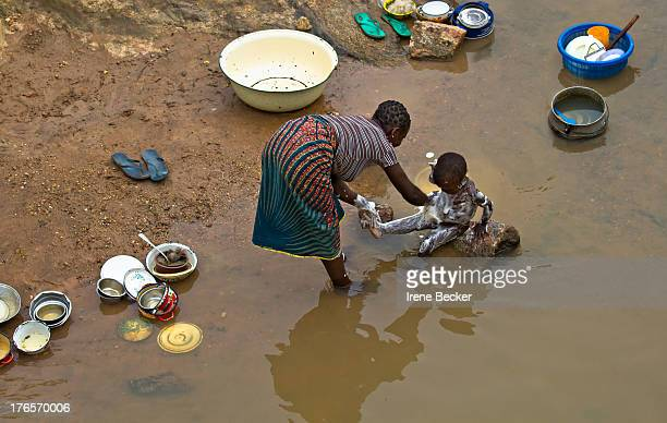 Woman bathing a child and washing the dishes in the river. Village southwest of Gurara Dam Reservoir, Kaduna State, Nigeria