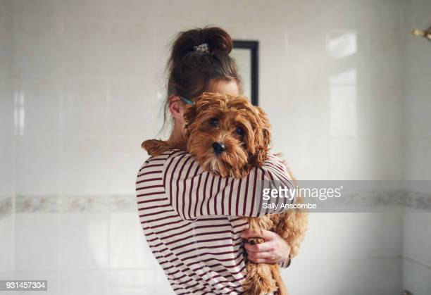 woman bathing her puppy - hund stock-fotos und bilder