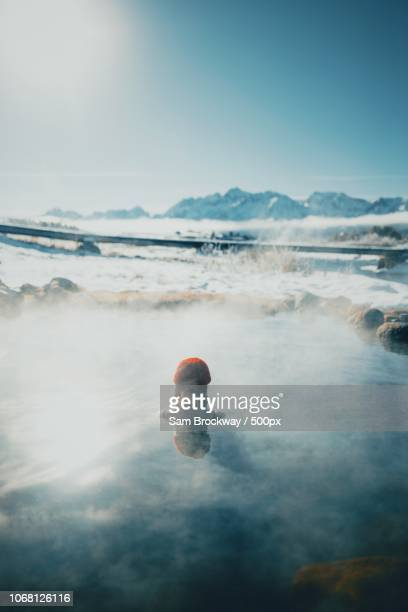 woman bathing in hot spring, sawtooth range in background, stanley, idaho, usa - hot spring stock pictures, royalty-free photos & images