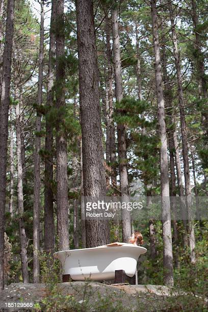 A woman bathing outdoors in the woods