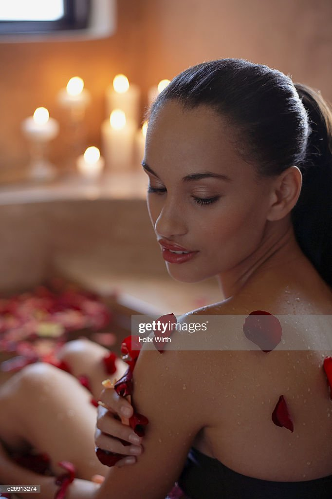 Woman bathing with flower petals : Stock-Foto