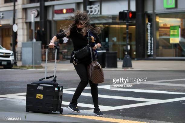 Woman battles the wind and rain in Copley Square in Boston, MA on September 30, 2020. Strong winds knocked down trees and utility poles across...