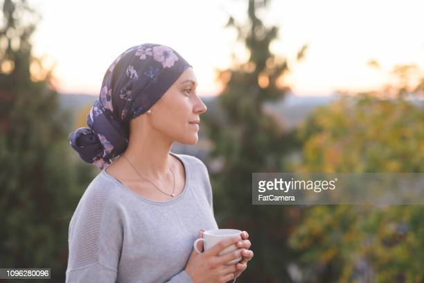 ethnic woman battling cancer stands outside and contemplates her life - survival stock pictures, royalty-free photos & images
