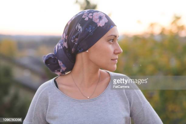 ethnic woman battling cancer stands outside and contemplates her life - pazienza foto e immagini stock