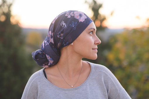 Ethnic woman battling cancer stands outside and contemplates her life 944834546