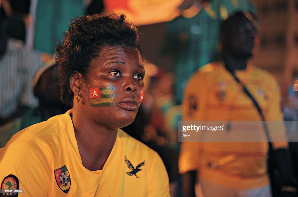 A woman bearing a flag of Togo on her cheek, watches the African Cup of Nation 2013 quarter final football match between Burkina Faso and Togo, in Lome, on February 3, 2013. Burkina Faso qualified for the semi-finals of the 2013 Africa Cup of Nations Sunday by pipping Togo 1-0 after extra time. AFP PHOTO / Daniel Hayduk