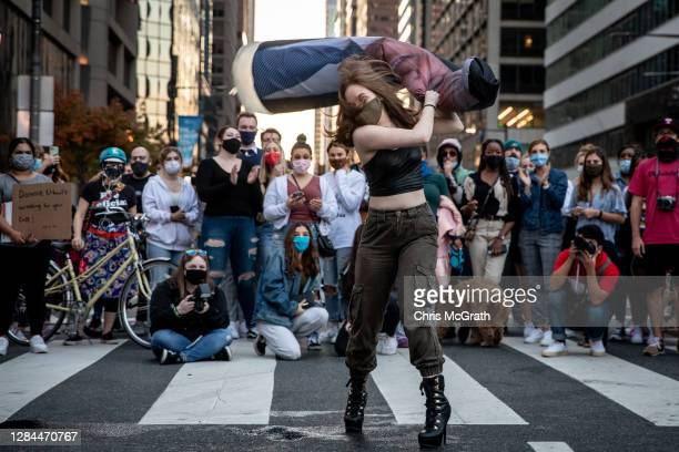 Woman beats an inflatable Donald Trump during celebrations after Joe Biden was declared winner of the 2020 presidential election on November 07, 2020...