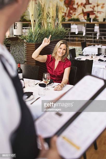 Woman beckoning to server in restaurant