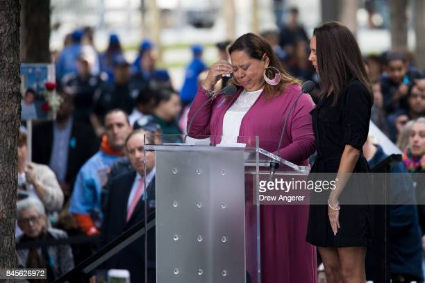A woman becomes emotional as she reads the names of victims during a commemoration ceremony for the victims of the September 11 terrorist attacks at...