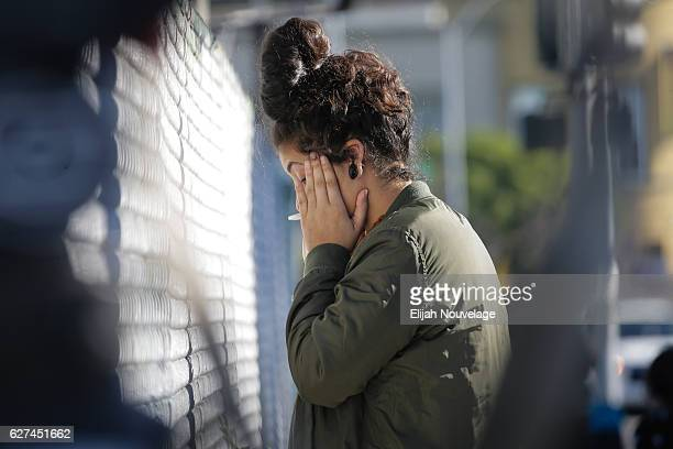 A woman becomes emotional while speaking on the phone near the scene following an overnight fire that claimed the lives of at least nine people at a...