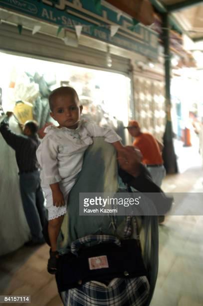 A woman beggar carrying her child in the main bazaar in central Jeddah Saudi Arabia 1st December 2005