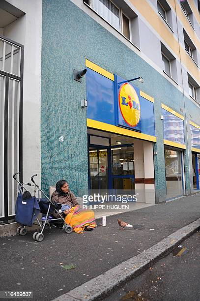 A woman begging sits on the floor at the entrance of a discount supermarket LIDL on June 16 2011 in the northern French town of Lille Six children...