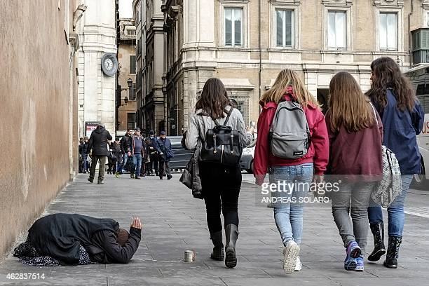 A woman begs along Piazza Venezia in central Rome on February 2015 Eurozone finance ministers will hold an extraordinary meeting in Brussels to...