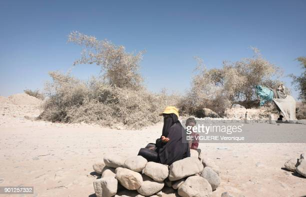 Woman begs along the road between Sanaa and Saada, the Houthi stronghold that was extensively bombed, displacing many of its civilians.