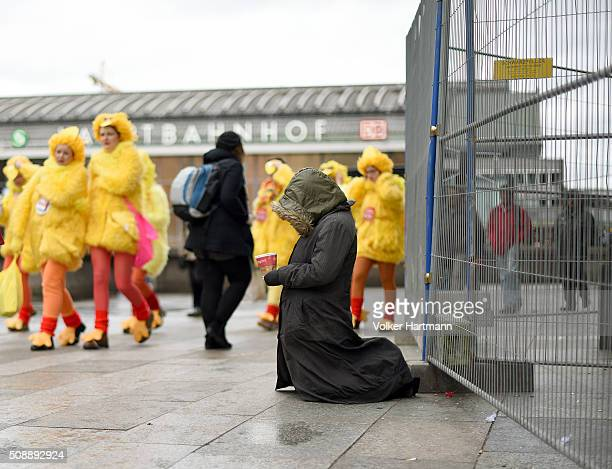 Woman begs for money in Front of Cologne Central Station during a carnival parade called 'Schull un Veedelszoech' as part of the carnival season on...