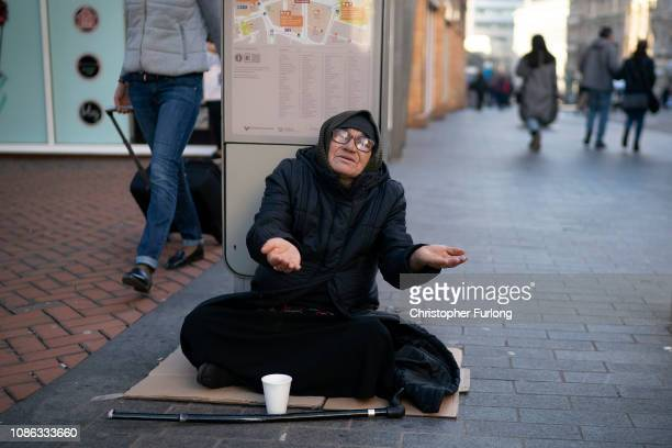 A woman begs on the street as shoppers make their last minute purchases on Christmas Eve on December 24 2018 in Birmingham England Financial...