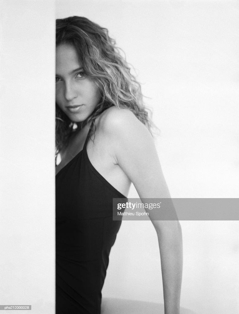Woman behind a wall, looking into camera, b&w. : Stockfoto