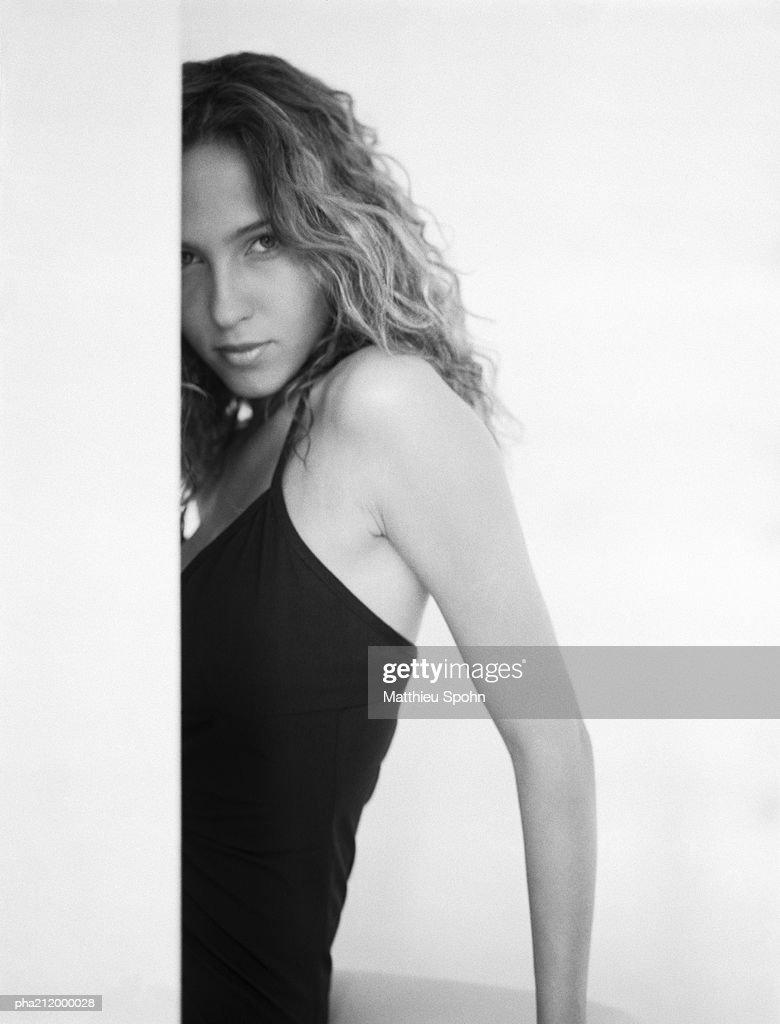 Woman behind a wall, looking into camera, b&w. : ストックフォト