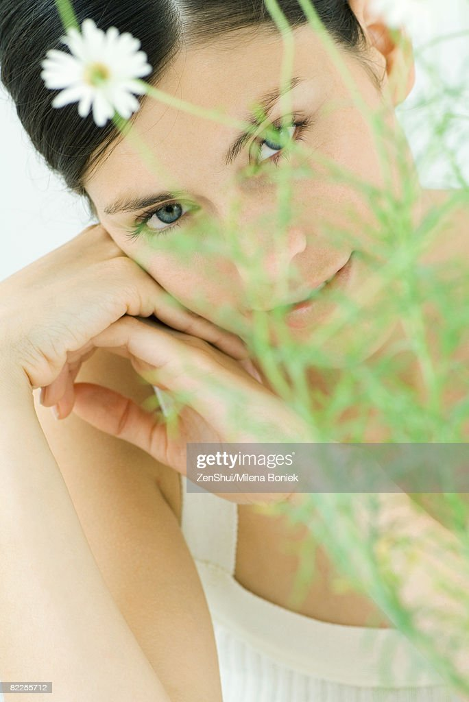 Woman behind chamomile plant, smiling at camera, portrait : Stock Photo