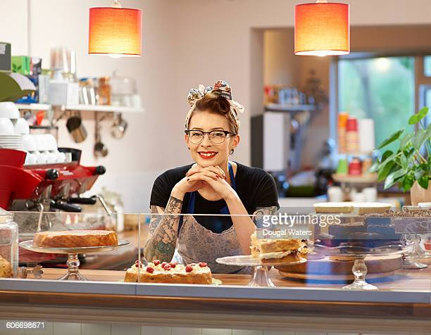 woman behind counter in cake shop. - bakery stock pictures, royalty-free photos & images