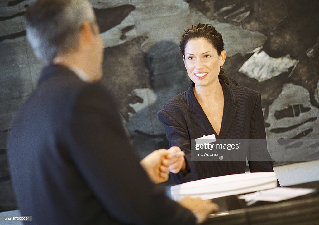 Woman behind counter smiling, handing object to man. : Stockfoto