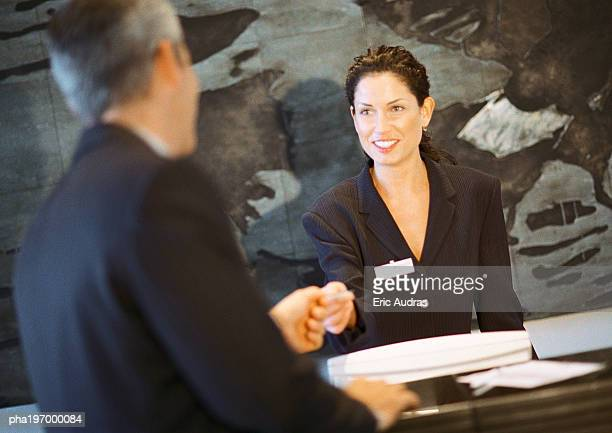 Woman behind counter smiling, handing object to man.