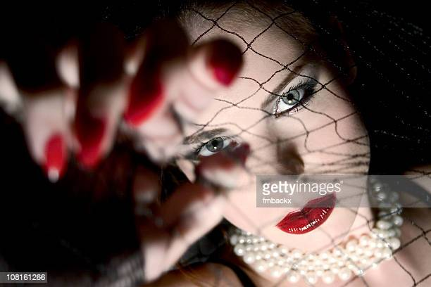 Woman Behind Fishnets with Long Red Nails