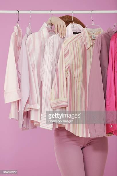 Woman behind hanging blouses