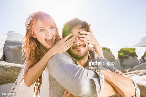 Woman behind man covering his eyes with hands smiling