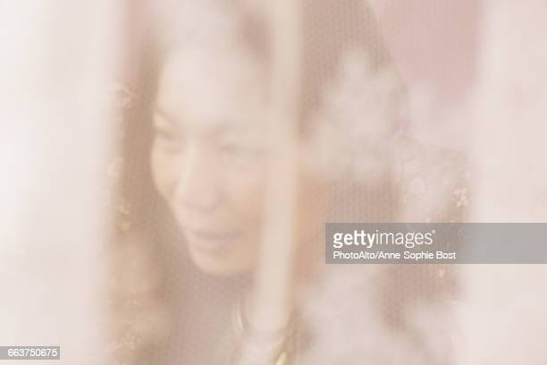 Woman behind mosquito netting