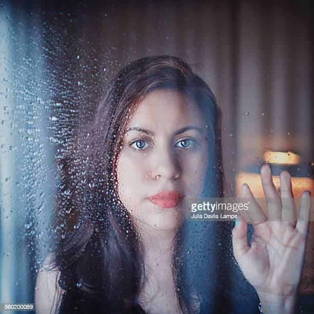 Woman behind rainy window
