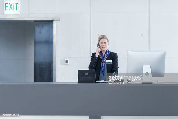 Woman behind reception desk in hotel lobby on the phone